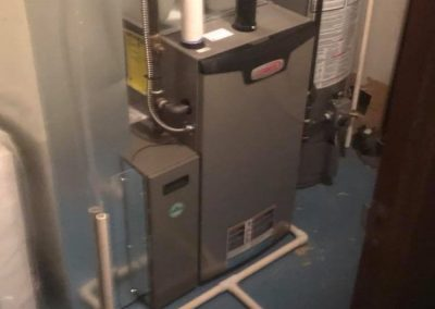 furnace installation in basement next to boiler